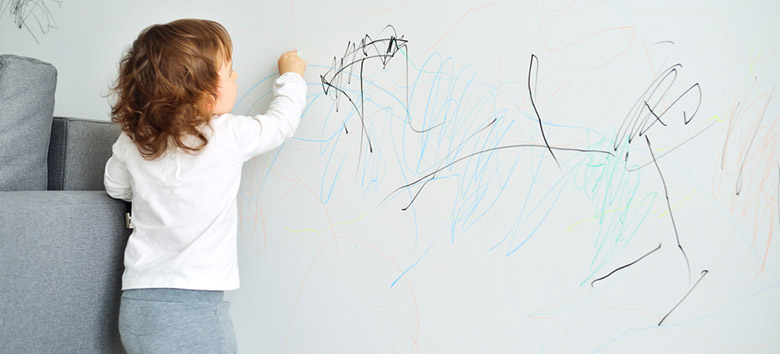 Little kid drawing with crayons on a wall.