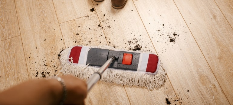 Mopping dirt off of a laminate floor.
